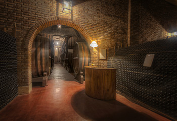 Wine bottles and casks in a winery cellar