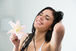 Woman washing herself with happy smile, lily flower and water sp