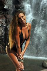Long hair sporty girl posing in front of waterfalls
