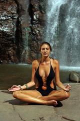 Beautiful girl wearing black one- piece swimsuit meditating