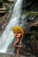 Girl posing in front of waterfalls with yellow umbrella