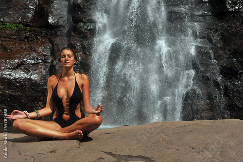 Beautiful girl wearing black one- piece swimsuit meditating