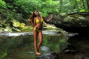 Sexy young woman posing in designer bikini at the mountain river