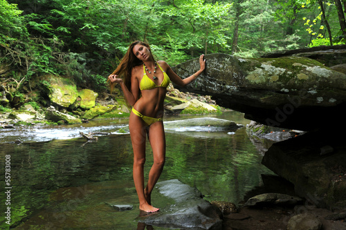 Sexy young woman posing in designer bikini at the mountain river