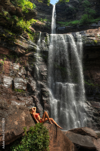 Beautiful slim fitness model posing sexy in front of waterfalls