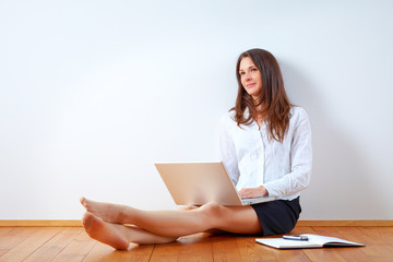 Young beauty with laptop sitting on the floor.