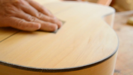Sanding a guitar, close up of luthier hands