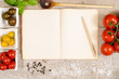 Altes Buch mit Werbefläche mit Bleistift, Kochlöffel und Tomat