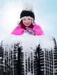 Cute girl with three snowy winter tyres in front of blue sky
