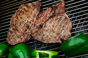 Steak with green peppers on a grill