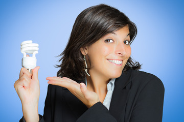 Young brunette woman shows energy saving bulb on blue background