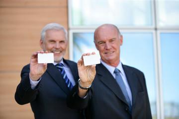 Two senior businessmen showing cards