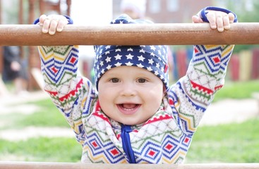 happy baby holding of climber on playground