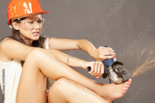 girl with helmet and goggles polished her nails with power tools