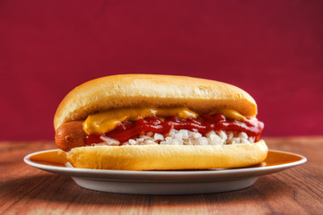 Hot dog on wooden table, red background