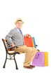 Senior man seated on a bench holding shopping bags