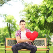 Smiling guy sitting on a bench and holding a red heart in park