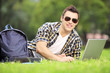 Smiling male lying on a grass and working on a laptop in a park