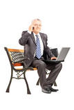 Mature businessman sitting on a bench and talking on a phone