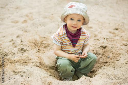 Kind sitzt im Sand auf dem Spielplatz