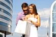 Девушка после шоппинга показывает покупки своему парню