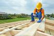 Roofer carpenter works on roof