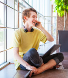 Cheerful smiling teenage boy talking by phone