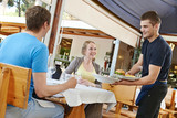 Fototapety waiter serving young people in restaurant