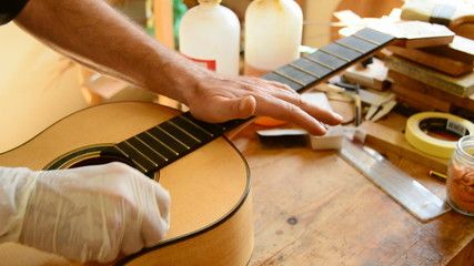 Luthier varnishing a guitar