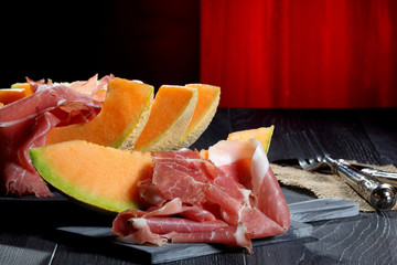antipasto  italiano prosciutto e melone sfondo rosso