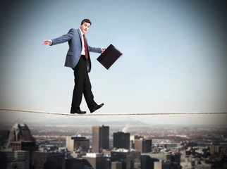 Businessman walking on rope.