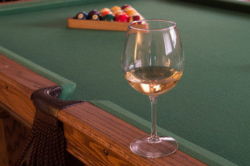 white wine in wine glass on pool billiards table