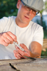 Caucasian man filling a syringe with soluble drug