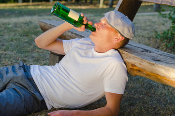 Alcoholic man drinking from a bottle of wine
