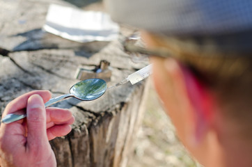 Addicted man preparing a dose with soluble heroin