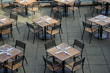 Wood tables and chairs set neatly for lunchtime