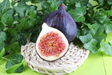 Ripe figs in leaves on wooden table close-up