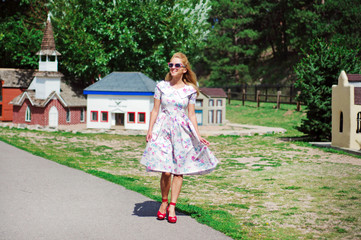 Young woman in a vintage dress, sunglasses and shoes