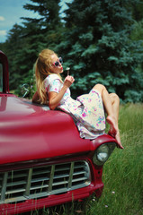 Young woman in vintage dress sitting on a red retro car © foreverbluebird