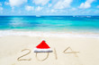 Number 2014 with christmas hat on the sandy beach
