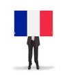 Smiling businessman holding a big card, flag of France