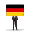 Smiling businessman holding a big card, flag of Germany