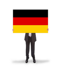 Smiling businessman holding a big card, flag of Germany