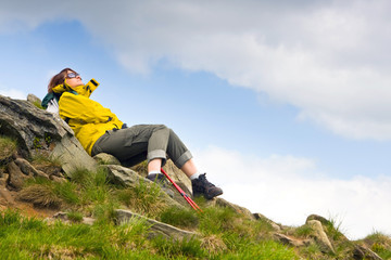 Hiker lady relaxing on a rock and looking to the horizon