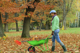 Woman raking autumn leaves in the garden