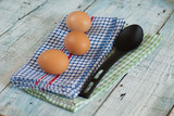 Eggs with spoon and dish towel