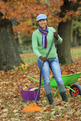 Autumn - woman raking autumn leaves in the garden