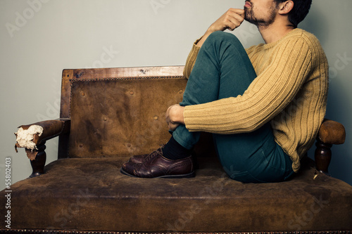 Young man thinking on the couch