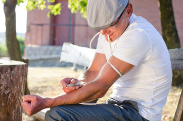 Addicted man injecting his tied arm intravenously