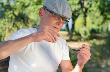 Addicted man filling a syringe with soluble heroin